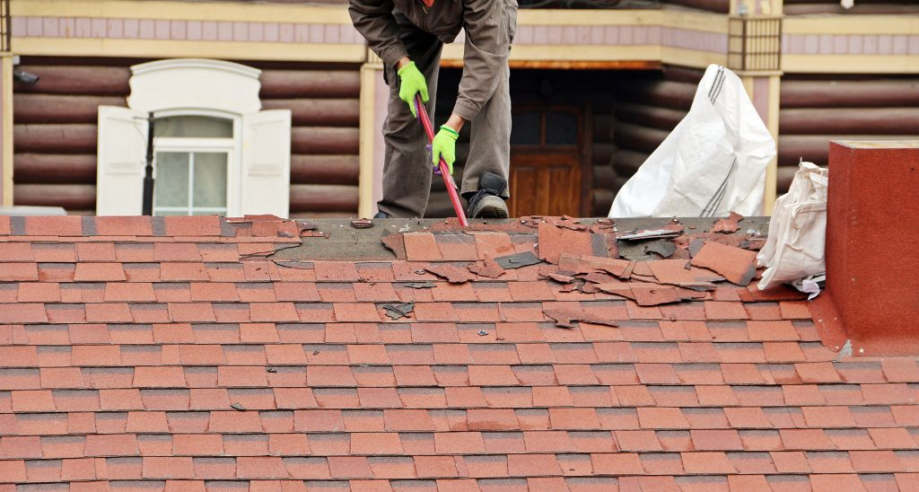 Worker Repairing a Red Tile Roof