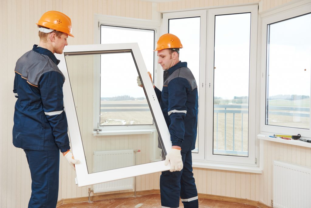 Two Workers Working on Installing Double Glass Windows