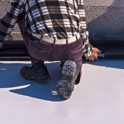 A Roofer Installs TPO Roofing.
