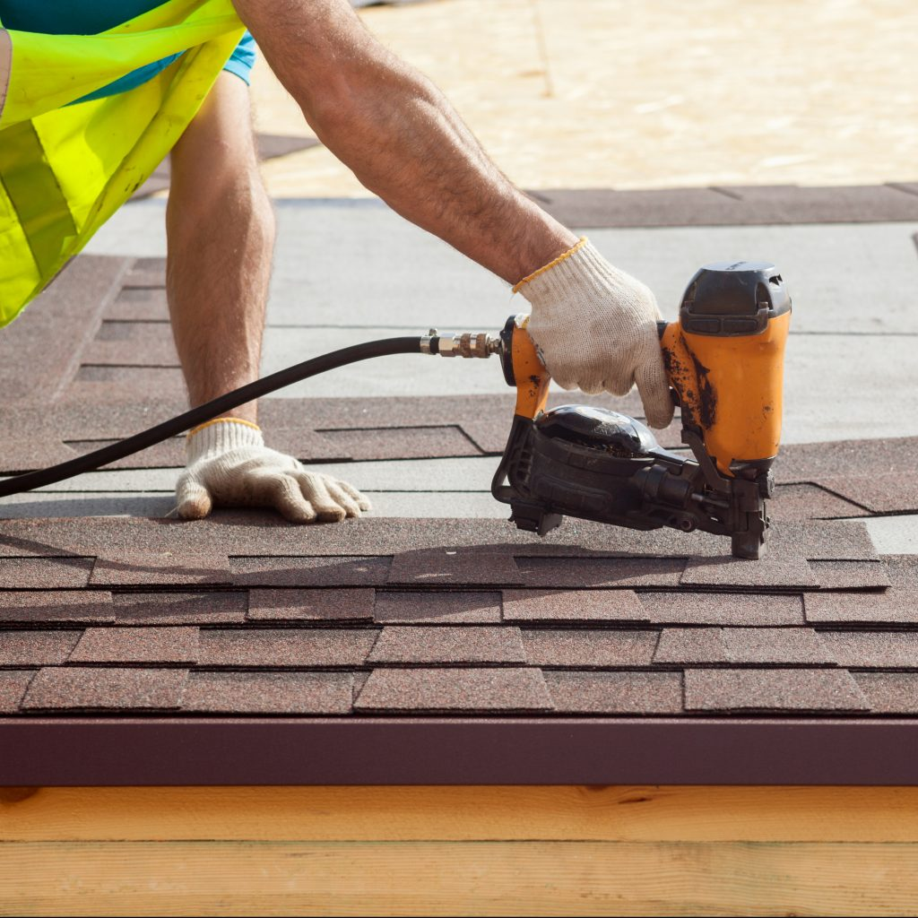 Construction Worker Installing Asphalt Shingles