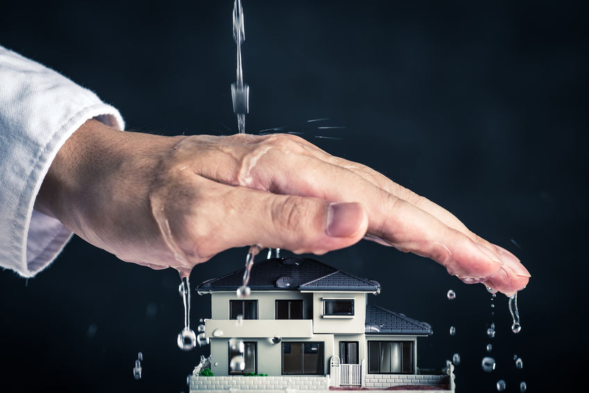 Hand Protecting Toy House From Water Flow